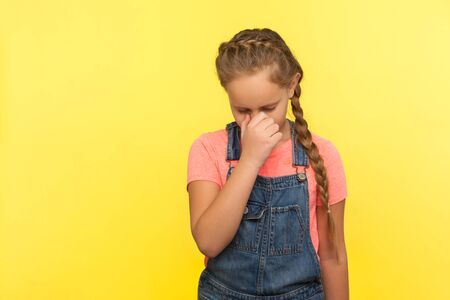 Portrait of unhappy little girl with braid in denim overalls hiding face down and crying, upset about loss or defeat, child feeling sorrow and regret. indoor studio shot isolated on yellow background