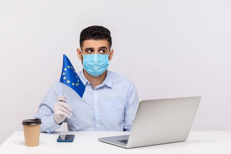 Pensive man in hygienic mask and gloves holding EU flag, looking worried and thoughtful, pondering to solve coronavirus problem, Covid-19 epidemic anxiety in Europe, quarantine. studio shot, indoor Stock Photo