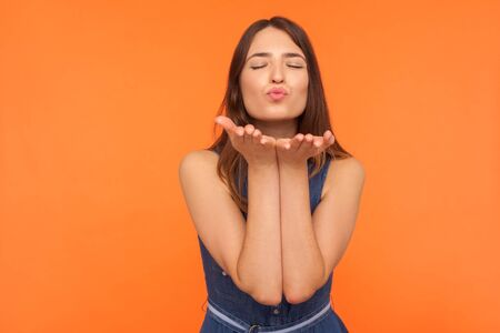 Cute romantic brunette woman standing with palms up and closed eyes in pleasure, sending amorous air kiss to camera, demonstrating affection, love. indoor studio shot isolated on orange background