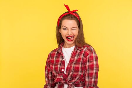 Portrait of optimistic pinup girl in checkered shirt and headband winking to camera with crazy naughty expression, showing tongue out, making faces blinking eye. retro 50's style, studio shot isolated