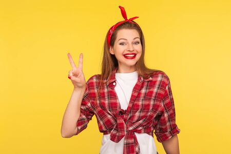 Optimism and success. Portrait of happy winner, pinup girl in checkered shirt and headband showing v sign or peace, victory gesture. retro vintage 50's style, studio shot isolated on yellow background