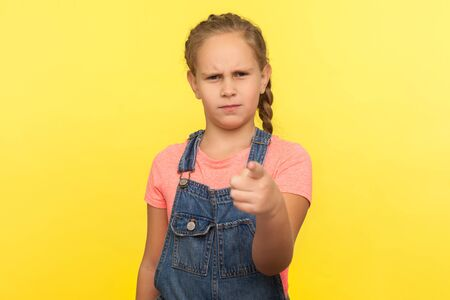 Hey you! Portrait of bossy little girl with braid in denim overalls pointing to camera and looking with angry displeased expression, making choice. indoor studio shot isolated on yellow background