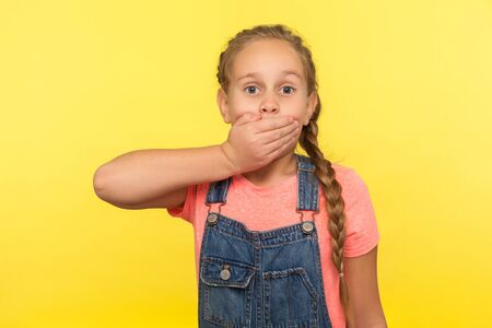 I won't tell! Portrait of scared little girl with braid in denim overalls covering mouth with hand, afraid to say secret, child terrified to speak. indoor studio shot isolated on yellow background