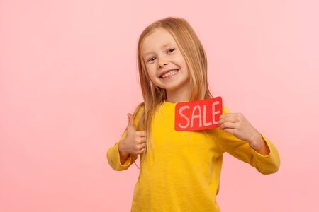 I like holiday discounts! Delighted happy little girl holding Sale inscription and showing thumb up, approving low prices in kid store, Black Friday. indoor studio shot isolated on pink background
