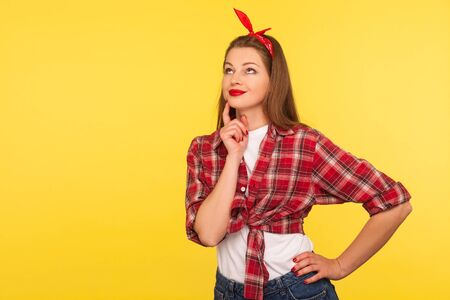 Portrait of pensive attractive pinup girl in checkered shirt and headband standing thoughtful, making decision, contemplating with confused doubtful expression, retro vintage 50's style. studio shot