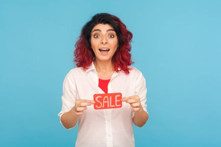 Portrait of amazed trendy woman with fancy red hair holding Sale word and looking at camera with shock and excitement, shopaholic surprised by discounts, low prices. studio shot blue background