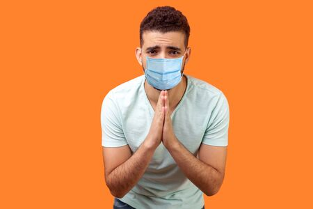 Please, I'm begging! Portrait of upset man with medical mask in white t-shirt holding arms in prayer, asking help or forgiveness with imploring eyes. indoor studio shot isolated on orange background Foto de archivo