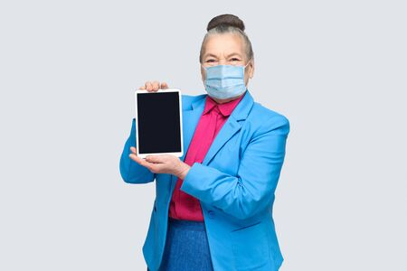 Aged woman with surgical medical mask holding and showing tablet screen. Grandmother in light blue suit with collected gray hair bun hairstyle. indoor studio shot, isolated on gray background