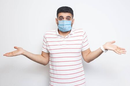 I don't know. Portrait of confused young man with surgical medical mask in striped t-shirt standing with raised arms and dont know what to do. indoor studio shot, isolated on white background.