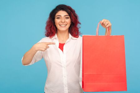 Portrait of happy shopaholic hipster woman with fancy red hair pointing big packages and smiling to camera, enjoying shopping, successful weekend sale. indoor studio shot isolated on blue background 写真素材