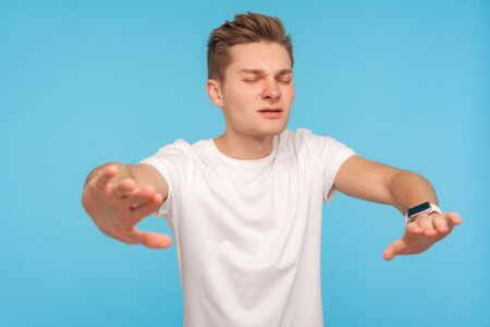 Blindness, lost in darkness. Upset man in t-shirt standing with closed eyes and outstretched hands, searching way, feeling frustrated and disoriented. indoor studio shot isolated on blue background