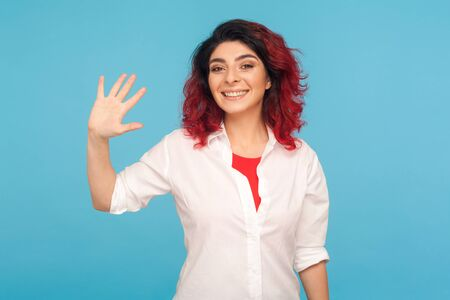 Hi, welcome! Portrait of happy friendly hipster woman with fancy red hair gesturing hello and smiling to camera, hospitable hostess meeting with joy. indoor studio shot isolated on blue background