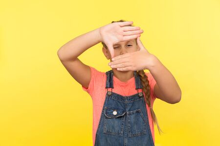 Portrait of little girl in denim overalls looking through photo frame hand gesture, focusing zooming picture, child observing world with interest. indoor studio shot isolated on yellow background Stok Fotoğraf
