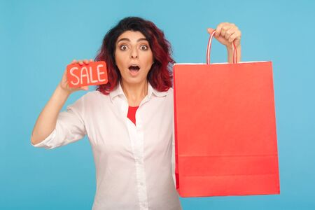 Unbelievable discount in fashion store. Nice cheerful hipster woman with fancy red hair showing sale word and shopping bags, enjoying black friday, low prices. indoor studio shot, blue background