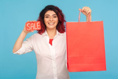 Discount in fashion store. Nice cheerful hipster woman with fancy red hair showing sale inscription and shopping bags, enjoying black friday, low prices. indoor studio shot isolated on blue background