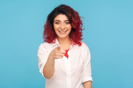 Hey you lucky! Portrait of happy hipster woman with fancy red hair in white shirt pointing finger to camera, choosing winner, gesturing we need you. indoor studio shot isolated on blue background