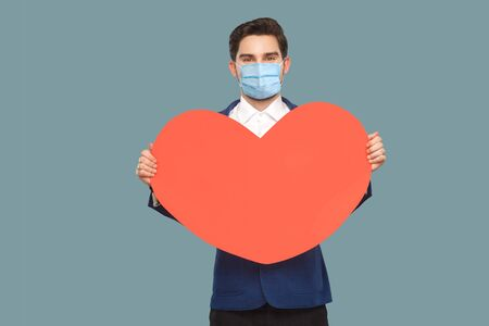 happy young man with surgical medical mask standing, holding red big heart shape. looking at camera with good feeling. medicine and health care concept. Indoor, studio shot isolated on blue background Stock Photo