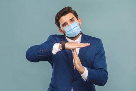 I need more time. Please, need time out. Body language. Portrait of pleading man with surgical medical mask and showing timeout gesture. Business people concept. Indoor, studio shot on blue background