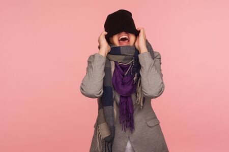 Portrait of angry mad girl in scarf pulling hat over her eyes and shouting, feeling crazy pissed off and desperate, autumn depression, nervous break down. studio shot isolated on pink background