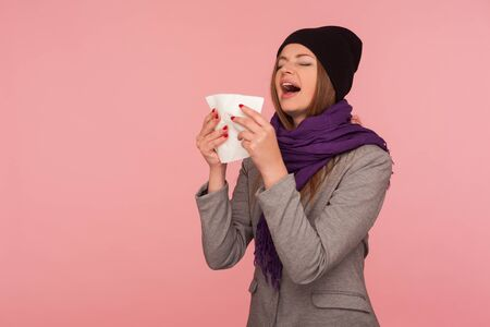 Influenza epidemic. Portrait of flu-sick woman in warm hat and scarf sneezing hard in napkin, blowing nose, suffering allergy symptom, feeling unhealthy. indoor studio shot isolated on pink background