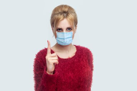 Portrait of serious young woman with surgical medical mask in red blouse standing and looking at camera with warning finger and alarming about health care. indoor shot isolated on gray background. Фото со стока