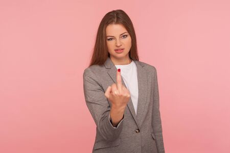 Portrait of irritated young woman in business suit showing middle finger, impolite rude gesture of disrespect, expressing hate and aggression in conflict. studio shot isolated on pink background