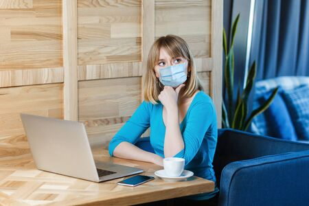 Portrait of thoughtful young blonde woman with surgical medical mask in blue t-shirt is sitting and working on laptop and thinking about her work. Indoor working, medicine and health care concept.