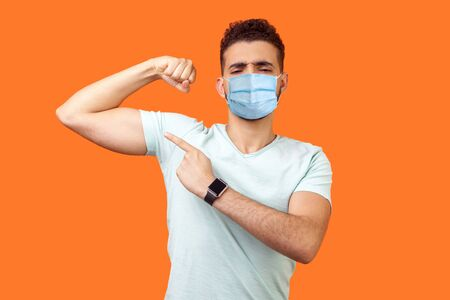 Look at my strength. Portrait of proud handsome brunette man with surgical medical mask pointing at biceps, feeling confident and powerful. indoor studio shot isolated on orange background