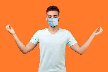 Practice mindfulness. Portrait of peaceful brunette man with surgical medical mask in white t-shirt doing meditation gesture with fingers, managing stress. indoor shot isolated on orange background Banque d'images