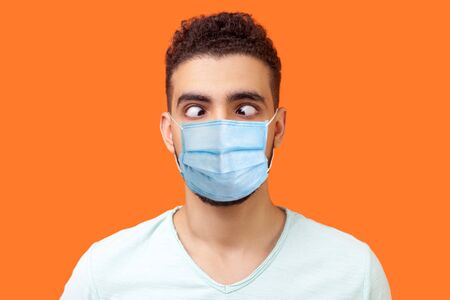 Portrait of comic crazy positive brunette man with surgical medical mask looking cross-eyed, having fun with silly face expression, playing fool. indoor studio shot isolated on orange background