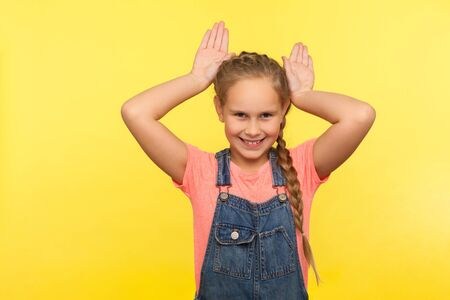 I'm rabbit! Portrait of adorable little girl in denim overalls showing bunny ears gesture, child having fun playing game and smiling to camera. indoor studio shot isolated on yellow background
