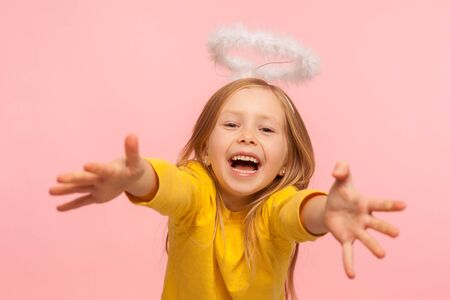 Delighted happy little girl with angelic halo screaming with happiness and reaching into camera to hug tightly, extremely glad to see you. Daughter missed and running to parent. studio shot, isolated