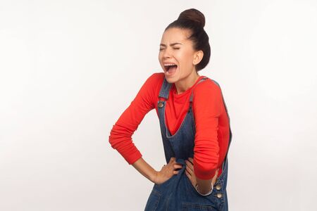 Acute abdominal cramps, gastrointestinal problem. Portrait of sick girl with hair bun in denim overalls shouting from acute stomachache, appendicitis, periods spasm. indoor studio shot, isolated Imagens