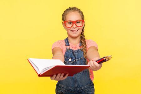 Portrait of clever creative little girl in red glasses holding notebook and pencils, school child smiling at camera showing homework, education concept. studio shot isolated on yellow background