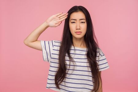 Yes sir! Responsible serious girl with brunette hair in striped t-shirt giving salute with attentive look, listening to command, ready to obey order. indoor studio shot isolated on pink background
