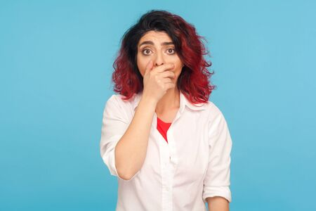 Portrait of scared hipster woman with fancy red hair covering mouth with hand and looking frightened at camera, intimidated victim afraid to tell truth. indoor studio shot isolated on blue background