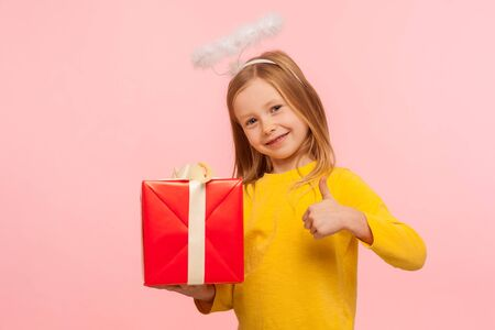 Portrait of nice kind little ginger girl with freckles and angelic halo over head holding gift box and showing thumb up, like gesture, approving charity. indoor studio shot isolated on pink background