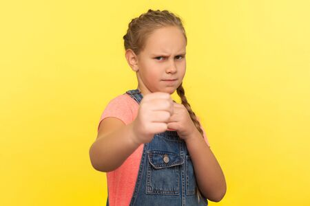 Portrait of brave fighting little girl in overalls standing with boxing gesture, frowning and holding fists to punch, angry child defending from offender. studio shot isolated on yellow background