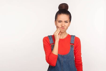 Portrait of unhealthy girl with hair bun in denim overalls touching sore cheek, suffering toothache, cavities or gum disease. indoor studio shot isolated on white background Banque d'images