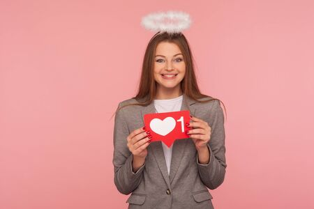 Portrait of adorable brunette woman with nimbus in business suit holding network heart Like icon and smiling to camera, recommending to follow blog. indoor studio shot isolated on pink background
