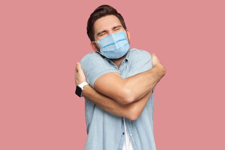 I love my self. Portrait of happy young man with surgical medical mask in blue shirt standing and hugging himself with closed eyes and smile enjoying. indoor studio shot, isolated on pink background.
