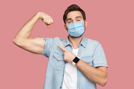I am strong and I can do anything. Portrait of proud young man with surgical medical mask in blue shirt standing pointing and showing his strong bicep. indoor studio shot, isolated on pink background.