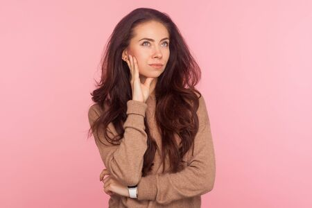 Portrait of confused puzzled thoughtful young woman with brunette wavy hair pondering difficult question, deciding having doubts, thinking over plan in mind. studio shot isolated on pink background