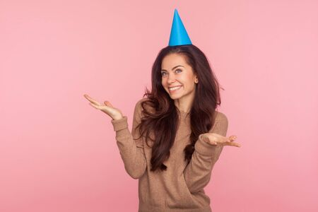 Portrait of delighted happy young woman with brunette wavy hair wearing funny cone and raising hands in surprise, looking wondered by birthday party. indoor studio shot isolated on pink background 版權商用圖片