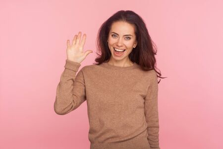Hi! Portrait of charming hospitable young woman with brunette hair waving hand, showing hello gesture and smiling friendly, greeting and welcoming guest. indoor studio shot isolated on pink background