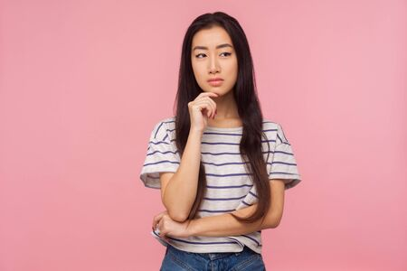 Portrait of cute pensive girl with long hair in striped t-shirt pondering decision, looking confused uncertain, having doubts while thinking over solution. studio shot isolated on pink background