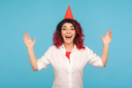 Excited amazed extremely happy woman with funny party cone on head raising hands, screaming joyfully with admiration, emotional reaction to birthday surprise. studio shot isolated on blue background Standard-Bild