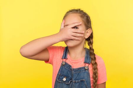 Portrait of inquisitive little girl with braid in denim overalls covering face with hand and looking through fingers, child shyly peeping at some secret. studio shot isolated on yellow background