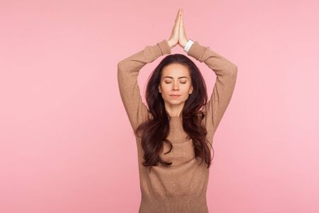 Meditation, mind balance. Portrait of peaceful concentrated young woman with brunette wavy hair holding hands in namaste gesture over head, doing yoga. indoor studio shot isolated on pink background Stock Photo