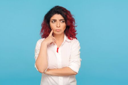 Thoughts and doubts. Portrait of confused pensive hipster girl with fancy red hair in white shirt pondering solution, thinking with serious puzzled look. indoor studio shot isolated on blue background